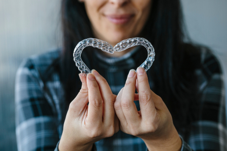 Patient Making Heart Shape with Dental Aligners